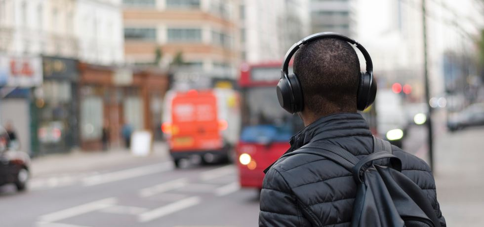 Man wearing headphones and waiting to cross the street.